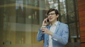 A filtração disparou do smartphone de fala do homem de negócios novo com a xícara de café no escritório moderno video estoque