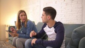 A filtração disparou na jovem mulher que usa os meios sociais no telefone celular que ignora seu sofá do sofá do noivo em casa co vídeos de arquivo