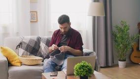 Filtração do homem novo que senta-se no sofá e no curso de confecção de malhas de observação no portátil filme