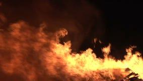 Filtração perto acima do fogo que queima-se no fumo e em logs pretos do fundo filme