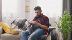 Filtrado del hombre sentándose en el sofá y haciendo punto en el hogar acogedor metrajes