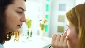 Filtrado del tiro de la mujer que aplica maquillaje al cliente joven del pelo rojo en la cámara lenta metrajes