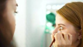 Filtrado del tiro de la mujer que aplica maquillaje a la cara roja del cliente del pelo en la cámara lenta metrajes