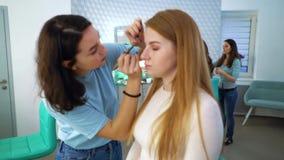 Filtrado del tiro de las muchachas del salón de belleza que hacen maquillaje y el peinado profesionales para las mujeres jovenes almacen de metraje de vídeo
