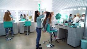Filtrado del tiro del equipo del salón de belleza que hace maquillaje y el peinado a las mujeres jovenes preciosas lindas metrajes