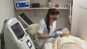 Filtrado encima del tiro del doctor o del terapeuta que administra el tratamiento fraccionario del laser de la piel para volver a imagen de archivo libre de regalías