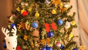 Filtrage sur le bel arbre de Noël avec des guirlandes et des boîte-cadeau de clignotement au fond du pin banque de vidéos