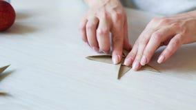 Filtrando o tiro das mãos da mulher que dobram a estrela do papel do origâmi para a decoração do Natal video estoque