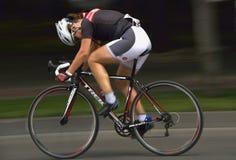 Filtração de uma bicicleta bonita da equitação da menina em um dia ensolarado, competindo para o evento grande de Prix da estrada Fotografia de Stock Royalty Free
