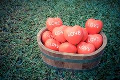 Filtre de vintage, beaucoup de coeur dans le seau en bois avec le mot d'amour dessus Image stock