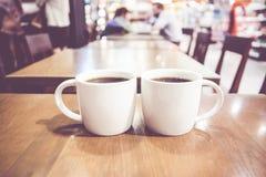 Filtre de vintage, couple de tasse de café blanc sur la table en bois avec le bl Photos stock