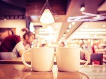 Filtre de vintage, couple de tasse de café blanc sur la table en bois avec le bl Photographie stock libre de droits