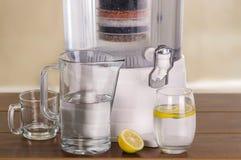 Filtre o sistema de purificador da água com dois vidros da água uma enchida até o meio com um limão interno e um vazio Foto de Stock