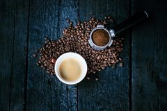 Filtre sans fond avec des haricots de morcellement sur une table et une tasse noires en bois de café d'expresso Grains de café rô image libre de droits