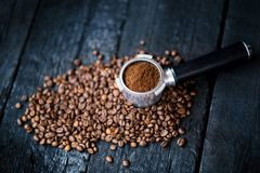 Filtre sans fond avec des haricots de morcellement sur une table noire en bois Grains de café rôtis Extraction de café d'expresso photo stock