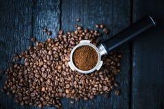 Filtre sans fond avec des haricots de morcellement sur une table noire en bois Grains de café rôtis Extraction de café d'expresso photos libres de droits