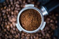 Filtre sans fond avec des haricots de morcellement sur une table noire en bois Grains de café rôtis Extraction de café d'expresso photographie stock libre de droits