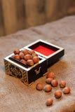 Filtrerad bild av hasselnötter i en träbunke Arkivbild