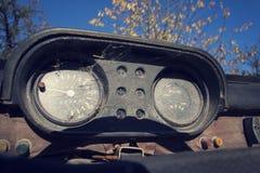 Filtrerat tappningfoto av den rostiga hastighetsmätaren på bilkontrollbordet Arkivfoto