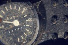 Filtrerat tappningfoto av den rostiga hastighetsmätaren på bilkontrollbordet Arkivbild