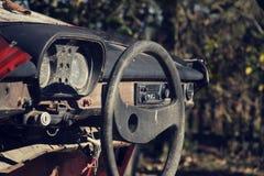 Filtrerat tappningfoto av styrninghjulet och den rostiga hastighetsmätaren på instrumentbrädan Royaltyfria Bilder