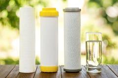 Filtres d'eau Cartouches de carbone et un verre de l'eau sur la table en bois sur le fond de nature Système de filtration de ména photo libre de droits