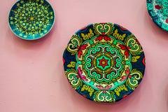 Filtrez les peintures multicolores avec le divers style accrochant sur le mur rose Objets faits maison traditionnels Image stock