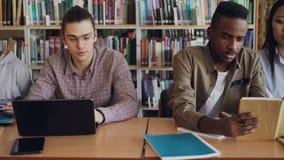 Filtri il colpo degli studenti concentrati multi gruppo etnico che parlano e che preparano per l'esame mentre si siedono alla tav video d archivio
