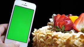 Filtri il colpo della torta di compleanno e della mano della frutta che tengono il telefono di schermo verde video d archivio