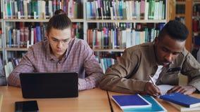 Filtri il colpo di multi gruppo etnico di studenti concentrati che preparano per l'esame mentre si siedono alla tavola in univers archivi video