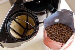 Filtro da caffè del canestro, macchinetta del caffè gocciolamento tipa e chicchi di caffè sul tavolo da cucina, vista superiore F fotografia stock libera da diritti