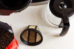 Filtro da caffè del canestro, macchinetta del caffè gocciolamento tipa e chicchi di caffè sul tavolo da cucina, vista superiore F fotografia stock