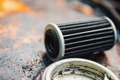 Filtro de aceite de motor viejo del lubricante en el garaje del coche Foto de archivo