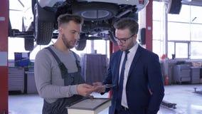 Filtro de ar do motor das negociações e da mostra do Mechanician ao cliente no fundo do automóvel em um elevador na estação do se vídeos de arquivo