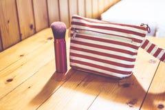 Filtro del vintage, bolso cosmético en la tabla de madera Fotografía de archivo