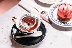 Filtrująca gorąca Jabłczana herbata słuzyć w porcelana rocznika filiżance z mousses tortem na marmuru wierzchołka stole obraz royalty free