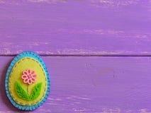 Filz-Ostereidekor mit rosa Blume auf einem hölzernen Hintergrund mit Kopienraum Spaß-Ostern-Handwerk für Kinder Fröhliche Ostern Lizenzfreie Stockbilder
