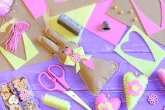 Filz-Osterhase mit Herzen Ostern-Wanddekoridee Scheren, Stifte, Threadspulen, Muffe, Knöpfe und Perlen in einem Kasten stockbild
