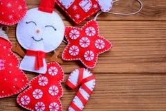 Filz-Weihnachtsdekorationen auf einem hölzernen Hintergrund mit Kopienraum für Text Filz-Weihnachtsbaum, Stern, Schneemann, Zucke Stockbild
