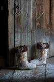 Filzstiefel nahe der Holztür Lizenzfreie Stockfotos