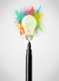 Filzstiftnahaufnahme mit farbiger Farbe spritzt und Glühlampe Lizenzfreies Stockbild