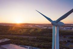 Fim aéreo disparado acima de uma turbina eólica na frente de um por do sol perfeito imagens de stock royalty free
