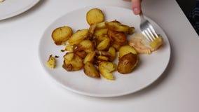 Fim acima As batatas fritadas são postas sobre uma forquilha e mergulhadas no molho de queijo filme