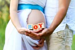 Fim-acima da barriga de uma mulher gravida e de seu HOL do marido fotografia de stock
