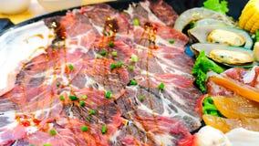 Fim acima da corrediça marmoreada crua fresca da carne de porco e do cogumelo dourado da agulha ou do cogumelo do enoki empilhado fotografia de stock royalty free
