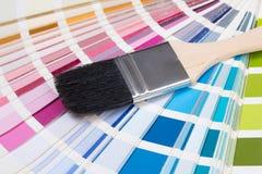 Fim acima da escova do pintor sobre a paleta colorida Fotos de Stock