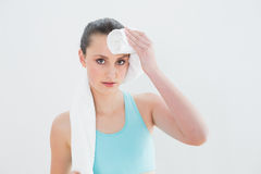Fim acima da limpeza da mulher suada com a toalha contra a parede fotografia de stock