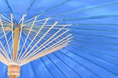 Fim acima da luz colorida - guarda-chuvas azuis com testes padrões de bambu da estrutura para o fundo foto de stock royalty free