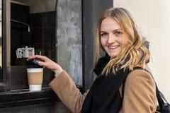 Fim acima da mão fêmea que toma o copo de papel do café quente imagem de stock