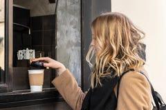 Fim acima da mão fêmea que toma o copo de papel do café quente fotos de stock royalty free